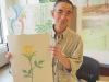 David, one of The Good Neighbours' Club's skillful artists, holds up a piece he made during art class.