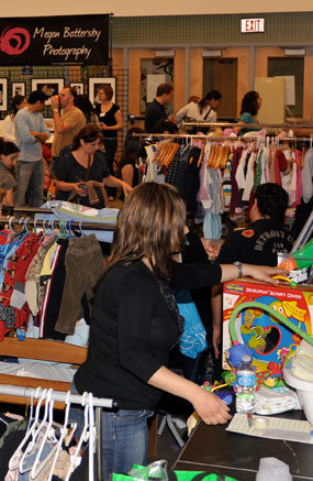 Mothers and fathers peruse the mountain of baby clothing, toys and accessories available at the Mom 2 Mom Sale.